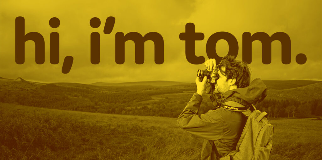 """Tom Ayling taking a photograph on Dartmoor hills with large text saying """"Hi, I'm Tom"""" behind."""